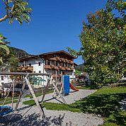 © Landhotel Tirolerhof/ Thomas Trinkl - Hotelansicht mit eigenem Kinderspielplatz