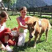 Pony und Kinder beim Spielen im Hotelgarten